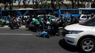 Sejumlah pengendara bergotong royong mengangkat sepeda motor mereka melewati pembatas jalan untuk berpindah jalur di kawasan Ridwan Rais, Jakarta, Rabu (21/8/2019). Pengendara motor tersebut berpindah jalur disebabkan tidak sabar menunggu kemacetan. (Liputan6.com/Johan Tallo)