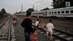 Anak-anak didampingi orang tuanya melihat kereta yang melintas saat menunggu waktu berbuka puasa atau ngabuburit di rel kereta Double Double Track (DDT) di Jakarta, Senin (21/5). (Merdeka.com/Iqbal S Nugroho)