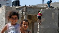Anak-anak bermain saat Hari Nakba di sebelah rumah mereka di kamp pengungsian Al-Shati, Jalur Gaza, Palestina, Rabu (15/5/2019). Hari Nakba di mana ratusan ribu rakyat Palestina eksodus dari tanah kelahirannya telah mengubah kehidupan mereka selama tujuh dekade terakhir. (MOHAMMED ABED/AFP)