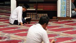 Sejumlah umat muslim bertadarus usai melaksanakan salat di Masjid Cut Meutia, Jakarta, Rabu (15/6/2016). Masjid Cut Meutia memiliki mihrab (tempat imam) yang diletakkan di samping kiri dari saf salat. (Liputan6.com/Helmi Fithriansyah)