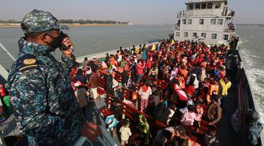 Pengungsi Rohingya duduk di kapal Angkatan Laut Bangladesh saat mereka dipindahkan ke pulau rawan banjir yang kontroversial, Bhashan Char di Teluk Benggala, di Chittagong (29/12/2020). Bangladesh mulai memindahkan pengungsi muslim Rohingya tahap kedua ke pulau terpencil tersebut. (AFP/Rehman Asad)
