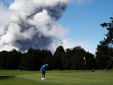 Doug Ralston bermain golf saat kepulan asap abu vulkanik berembus dari puncak gunung Kiluaea di Volcano, Hawaii (21/5). Lava dari gunung Kilauea Hawaii mengalir ke laut dan memicu reaksi kimia yang menciptakan asap hitam. (AP Photo/Jae C. Hong)