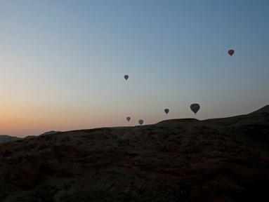Sejumlah balon udara yang membawa wisatawan terbang saat matahari terbit di atas kota Luxor, Kairo, Mesir (13/12). Luxor adalah sebuah kota modern yang terletak di kedua tepi timur dan barat Sungai Nil di Mesir bagian utara. (Reuters/Amr Abdallah Dalsh)