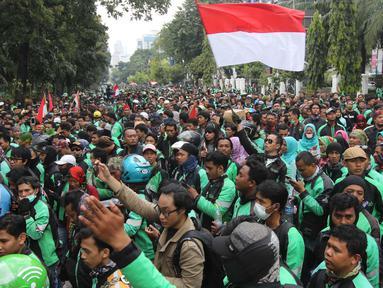 Ribuan pengemudi ojek online melakukan aksi di seberang Istana Merdeka, Jakarta, Selasa (27/3). Dalam aksinya mereka menuntut pemerintah melakukan penetapan tarif standar dengan nilai yang wajar. (Liputan6.com/Arya Manggala)