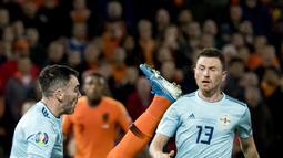 Pemain Belanda Donyell Malen (tengah) berebut bola dengan pemain Irlandia Utara Michael Smith (kiri) pada laga kualifikasi Euro 2020 di Rotterdam, Belanda, Kamis (10/10/2019). Belanda menang 3-1 dengan dua gol di antaranya dicetak Memphis Depay. (Koen van Weel/ANP/AFP)