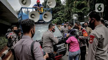 Petugas kepolisian beradu argumen saat memberhentikan mobil komando aksi di sekitar Gedung DPR, Jakarta, Jumat (14/8/2020). Polda Metro Jaya melarang adanya unjuk rasa di depan Gedung DPR/MPR yang bertepatan dengan sidang tahunan. (Liputan6.com/Faizal Fanani)