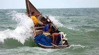 Sebuah perahu nelayan tradisional mencoba menembus gelombang di kawasan laut penghubung pantai Selat Malaka Lhokseumawe Propinsi Aceh. (ANTARA)