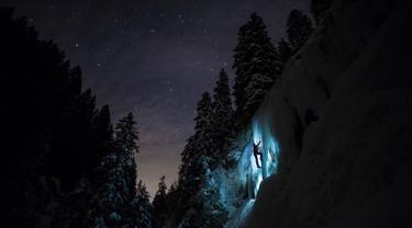 Anggota tim Arnica, Pierre mendaki tebing es saat sesi latihan malam hari di dekat La Lecherette, Hongrin, Kota Vaud, Swiss, Rabu (14/2). Pierre mendaki di bawah malam yang penuh bintang. (Anthony Anex/Keystone via AP)