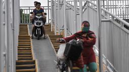 Pengendara sepeda motor melintasi JPO di Jalan Yos Sudarso, Jakarta, Senin (12/11). Aksi nekat yang dilakukan para pengendara sepeda motor demi mempersingkat rute jalan tersebut sangat mengganggu kenyamanan pejalan kaki. (Merdeka.com/Iqbal S. Nugroho)