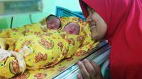 Istri Alfiat (asisten pelatih Persik) bersama si kembar buah hati mereka yang baru lahir. (Bola.com/Gatot Susetyo)