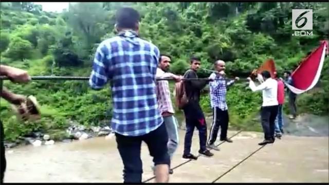 Penduduk desa dan orang-orang yang merayakan festival Hindu di India terpaksa menyeberangi sungai yang banjir dengan tali.