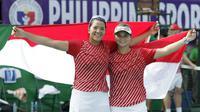 Petenis ganda putri Indonesia, Beatrice Gumulya dan Jessy Rompies, merayakan kemenangan di final SEA Games 2019 di Rizal Memorial Tennis Court, Sabtu (7/12/2019). (Bola.com/Muhammad Iqbal Ichsan)