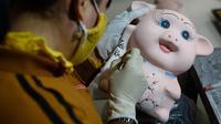 Perajin melukis patung babi yang terbuat dari tanah liat menjelang Tahun Baru Imlek atau Tet di sebuah bengkel, Hanoi, 23 Januari 2019. Penduduk Vietnam bersiap merayakan Tahun Baru Imlek 2019 yang merupakan tahun shio babi tanah. (Nhac NGUYEN/AFP)
