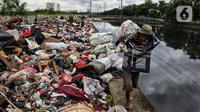 Warga membawa sampah sisa banjir yang dikumpulkan dari sepanjang Kali Cengkareng, Jakarta Barat, Kamis (9/1/2020). Tumpukan sampah di sepanjang bantaran kali dan rumah-rumah warga terlihat setelah banjir yang melanda sejumlah kawasan Jakarta mulai surut. (Liputan6.com/Johan Tallo)