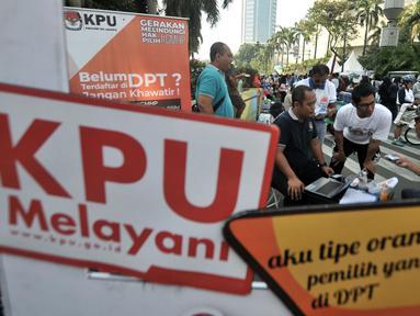 Petugas KPU DKI membuka stan pendaftaran daftar pemilih tetap (DPT) di kawasan Car Free Day, Jakarta, Minggu (21/10). Pendaftaran ini dibuka hingga 28 Oktober dengan syarat membawa fotocopy e-KTP dan Kartu Keluarga. (Merdeka.com/Iqbal S. Nugroho)