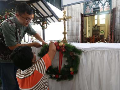 Umat kristen dan pengurus menata dekorasi di Gereja Katedral, Jakarta, Sabtu (23/12). Jelang perayaan natal Gereja Katedral mulai bebenah dan dipercantik untuk keperluan ibadah natal. (Liputan6.com/Angga Yuniar)