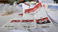 Pekerja menunjukkan surat suara yang terpotong di Gedung Logistik KPU Kota Jakarta Pusat, Jakarta, Selasa (5/3). Sebanyak 60 persen surat suara rusak akibat terpotong atau tidak simetris dan bercak noda. (merdeka.com/Iqbal Nugroho)