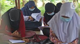 Sejumlah murid SMP Sekolah Alam mengikuti Ujian Akhir Semester (UAS) di Sukawangi, Kabuapaten Bekasi, Jawa Barat, Senin (30/11/2020). Menurut pengurus Sekolah Alam KBM tatap muka  jenjang pendidikan SD,SMP, dan SMA tetap berjalan dengan menerapkan protokol kesehatan. (Liputan6.com/Herman Zakharia)