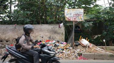 Pengendara melintasi tumpukan sampah rumah tangga di Jalan Raya Tanah Baru kawasan Depok, Jawa Barat, Rabu (15/5/2019). Kurangnya tempat penampungan membuat warga terpaksa membuang sampah di lokasi tersebut, meskipun menimbulkan bau tidak sedap serta mengotori jalan. (Liputan6.com/Immanuel Antonius)