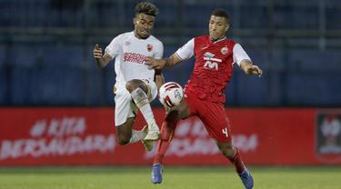 Pemain Persija Jakarta, Yann Motta Pinto (kanan), berebut bola dengan pemain PSM Makassar, Yakob Sayuri, dalam pertandingan Babak Penyisihan Piala Menpora 2021 di Stadion Kanjuruhan, Malang. Senin (22/3/2021). (Bola.com/Arief Bagus)