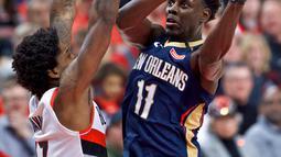 Aksi pemain Pelicans, Jrue Holiday (kanan) melakukan tembakan melewati adangan pemain  Blazers, Ed Davis pada laga Playoffs game ke-2 NBA basketball di Moda Center, Portland, (17/4/2018). Pelicans menang 111-102. (AP/Craig Mitchelldyer)