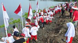 Sejumlah siswa SD Nasima Semarang menanam pohon mangrove di Teluk Pantai Mangunharjo, Mangkang, Tugu, Jumat (18/1). Data Kementerian Kehutanan, sekitar 60 persen kondisi hutan mangrove di pantai utara Pulau Jawa dalam keadaan rusak. (Liputan6.com/Gholib)