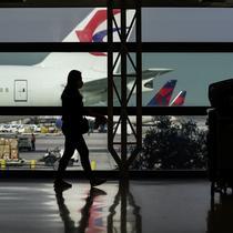 Siluet pelancong dengan masker di samping kopernya di Bandara Internasional Los Angeles di Los Angeles, California, 23 November 2020. Sekitar 1 juta orang Amerika memadati bandara dan pesawat menjelang libur Thanksgiving pekan ini bahkan saat kematian akibat COVID-19 melonjak. (AP Photo/Jae C. Hong)