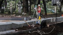 Pekerja melakukan pengukuran saat menyelesaikan proyek pembangunan mass rapid transit (MRT) fase II rute Bundaran HI-Kota di Taman Monumen Nasional (Monas), Jakarta, Selasa (2/7/2019). Seluruh stasiun MRT fase II akan berada di bawah tanah.(Www.sulawesita.com)