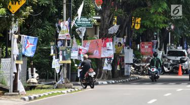 Sejumlah alat peraga kampanye (APK) calon anggota legislatif (caleg) memenuhi pepohonan yang berada di pinggir jalan, Jakarta, Rabu (20/3). Pemasangan APK tersebut melanggar aturan PKPU Nomor 23 Pasal 31 Tentang Bahan Kampanye. (merdeka.com/Iqbal Nugroho)