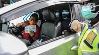 Pengendara menunjukkan brosur berisi imbauan larangan mudik dari polisi  saat sosialisasi di kawasan Bundaran HI, Jakarta, Rabu (6/5/2020). Sosialisasi tersebut dilakukan demi memutus mata rantai penyebaran virus corona COVID-19 dari satu wilayah ke wilayah lain. (Liputan6.com/Faizal Fanani)