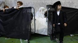 Pengantin Yahudi ultra-ortodoks Hannah Halbershtam memasuki bagian pria saat melangsungkan upacara pernikahan di kota ultra-ortodoks Bnei Brak, Israel, Selasa (20/8/2019. (AP Photo/Oded Balilty)