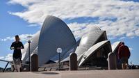 Warga berjalan dekat Gedung Opera di Sydney, Australia, Sabtu (26/6/2021). Pihak berwenang melakukan lockdown beberapa area pusat kota terbesar di Australia untuk menantisipasi penyebaran virus corona COVID-19 varian Delta yang sangat menular. (Saeed KHAN/AFP)
