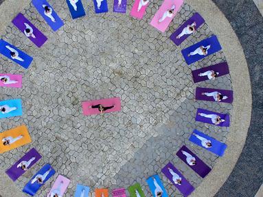 Foto udara menunjukkan penggemar yoga melakukan latihan menjelang Hari Yoga Internasional di sebuah taman di Handan, provinsi Hebei, China, Jumat (19/6/2020). Hari Yoga Internasional atau International Day of Yoga diperingati setiap tahun pada 21 Juni. (Photo by STR / AFP)