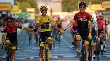 Pebalap Kolombia Egan Bernal (tengah) berpegangan tangan dengan Geraint Thomas setelah memenangkan balap sepeda Tour de France 2019, Paris, Prancis, Minggu (28/7/2019 ). Egan Bernal menjuarai Tour de France 2019 setelah menempuh perjalanan lebih dari 3,409 km. (AP photo/Michel Euler)