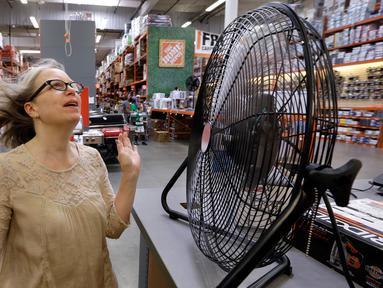 Davi Sobotta bereaksi saat mencoba kipas meja menjelang gelombang panas di toko perlengkapan Home Depot di Seattle, Selasa (1/8). Peringatan cuaca panas yang berlebihan untuk wilayah itu dimulai pada Selasa sore dan hingga Jumat malam (AP/Elaine Thompson)