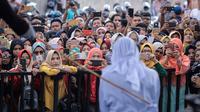 Antusiasme warga saat menyaksikan hukum cambuk terhadap pekerja seks komersial (PSK) online di halaman Masjid Jamik Lueng Bata, Banda Aceh, Aceh, Jumat (20/4). Dua PSK online masing-masing mendapat hukuman 11 kali cambukan. (AP Photo/Heri Juanda)