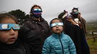 Keluarga Adat Mapuche menggunakan kacamata khusus untuk mencoba mengamati gerhana matahari total di Carahue, La Araucania, Chile, Senin (14/12/2020). Gerhana matahari total terlihat dari Chile dan wilayah Patagonia utara Argentina. (AP Photo/Esteban Felix)