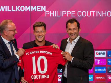 Pemain baru Bayern Munchen Philippe Coutinho (tengah) memegang jersey timnya bersama CEO Karl-Heinz Rummenigge (kiri) dan pelatih Hasan Salihamidzic saat konferensi pers di Munich, Jerman, Senin (19/8/2019). Coutinho resmi menjadi pemain Bayern Munchen musim 2019-2020. (Peter Kneffel/dpa via AP)