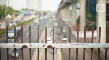 Kondisi pagar JPO yang melintang di atas jalan tol dalam kota dan Jalan Gatot Soebroto di Mampang, Jakarta, Selasa (4/2/2020). Kurangnya perawatan menyebabkan kondisi pagar JPO tersebut banyak yang berkarat sehingga berpotensi membahayakan pejalan kaki yang melintas. (Liputan6.com/Immanuel Antonius)