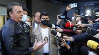 Presiden Brasil Jair Bolsonaro memberikan keterangan dalam konferensi pers di Rumah Sakit Vila Nova Star di Sao Paulo, Minggu (18/7/2021). Jair Bolsonaro diizinkan meninggalkan rumah sakit setelah dirawat selama empat hari karena ususnya tersumbat. (Miguel SCHINCARIOL / AFP)