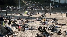 Penduduk dan turis duduk di pantai berpasir selama cuaca musim dingin yang hangat di Biarritz di Perancis barat (17/2). Kawasan pantai Biarritz yang berbatasan dengan Spanyol ini termasuk salah satu wilayah termahal di Prancis. (AFP Photo/Iroz Gaizka)