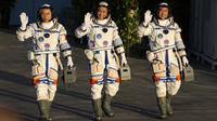 (kiri-kanan) Astronaut China Tang Hongbo, Nie Haisheng, dan Liu Boming melambai saat bersiap untuk lepas landas dari Pusat Peluncuran Satelit Jiuquan, China, Kamis (17/6/2021). Para astronaut menuju Tianhe, modul awal stasiun ruang angkasa Tiangong (Istana Surgawi) China. (AP Photo/Ng Han Guan)