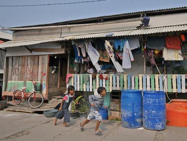 Anak-anak berlari melewati tong air di kawasan Kampung Kamal Muara, Jakarta, Selasa (9/7/2019). Sebagian besar warga Kampung Kamal Muara memasang pipa pada talang air di tepi atap rumah mereka untuk menampung air hujan. (Liputan6.com/Herman Zakharia)