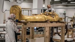 Para arkeolog merestorasi sarkofagus atau peti mati emas Firaun Tutankhamun di laboratorium restorasi Grand Egyptian Museum (GEM), Giza, Mesir, Senin (13/4/2020). Firaun Tutankhamun merupakan Raja Mesir Kuno yang memerintah antara tahun 1342-1325 SM. (Khaled DESOUKI AFP)