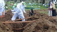 Seorang perempuan mengambil gambar proses pemakaman jenazah korban COVID-19 di TPU Tegal Alur, Jakarta, Kamis (17/12/2020). Hingga hari ini, intensitas pemakamanan korban covid-19 di DKI masih tinggi dengan rata-rata yang dimakamkan mencapai 30 hingga 38 jenazah per hari. (merdeka.com/Arie basuki)