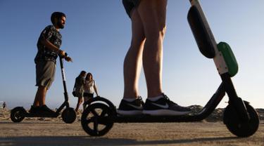 Pengendara menaiki skuter listrik  di sepanjang Venice Beach, Los Angeles, 13 Agustus 2018. Beberapa penduduk kota mengeluhkan skuter-e yang kontroversial karena membahayakan pejalan kaki dan terkadang menyumbat trotoar. (Mario Tama/Getty Images/AFP)