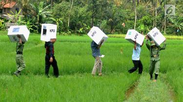 Petugas Kelompok Penyelenggara Pemungutan Suara (KPPS) membawa logistik Pemilu 2019 melintasi sawah menuju TPS di Desa Cidokom, Bogor, Selasa (16/4). Pada 17 April 2019, masyarakat dapat menunaikan haknya mencoblos, baik untuk memilih caleg maupun presiden-wakil presiden. (Merdeka.com/Arie Basuki)