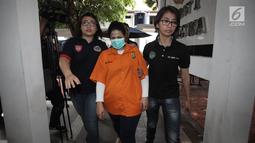Artis Dhawiya Zaida dikawal petugas saat rilis di Polda Metro Jaya, Jakarta, Sabtu (17/2). Total barang bukti yang diamankan sabu seberat 1,32 gram beserta sejumlah alat hisap dan barang bukti lainya. (Liputan6.com/Arya Manggala)