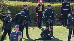 Seorang anggota The Rifles terjatuh menjelang pemakaman Pangeran Philip di luar Kapel St George di Kastil Windsor, Windsor, Inggris, Sabtu (17//4/2021). Seorang prajurit dekatnya berusaha menangkapnya saat rekannya jatuh. (Arthur Edwards/Pool via AP)