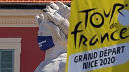 Logo Tour de France 2020 terlihat di dekat patung bermasker di kota Nice, French Riviera, Rabu (26/8/2020). Ajang balap sepeda lintas kota di Prancis kali ini akan dimulai dari kota Nice pada 29 Agustus hingga 20 September di bawah bayang-bayang 'gelombang kedua' COVID-19. (Kenzo Tribouillard/AFP)